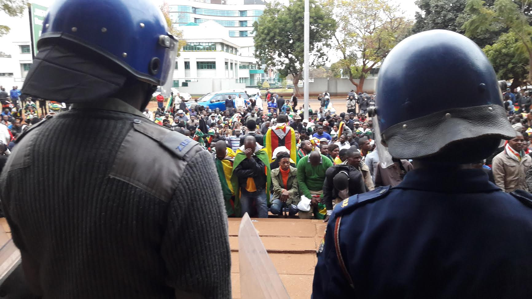 Zimbabwean police watch as protesters gather outside the court. Credit: Simon Allison.
