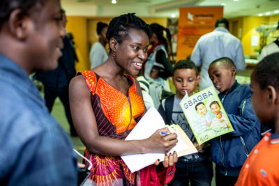 Robtel Neajai Pailey with her kids anti-corruption book Gbagba at the Africa Writes festival. Credit: Ivan Gonzalez.