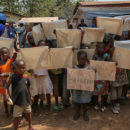 "Children in the capital Bangui hold up signs reading ""Peace"" and ""Love"". Credit: UN Photo/Nektarios Markogiannis."