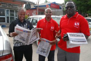 Ansbert Ngurumo (left) reads one of the newspapers he previously edited. Credit: John Dande.
