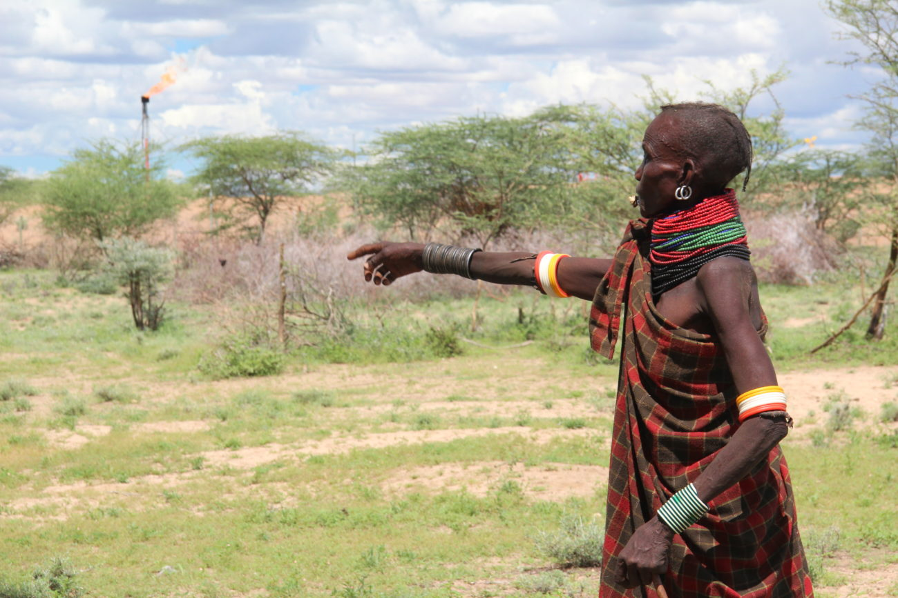 A woman herder in Nakukulas, Turkana county, with a gas flare in the distance. Credit: Nick Young.