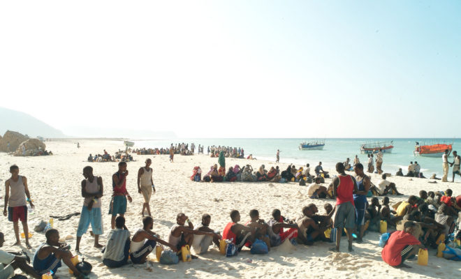 Refugees and migrants line up on a Somalia beach to board the boats that will take them across the Gulf of Aden to Yemen. In a military style operation, the passengers board the small smugglers' boats in groups of 10. The overcrowded boats can take days to cross. Credit: Alixandra Fazzina.