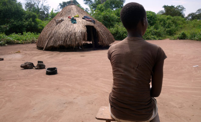 A girl formerly associated with opposition forces, sits outside her home in Bakiwiri, Yambio. Credit: Child Soldiers International.