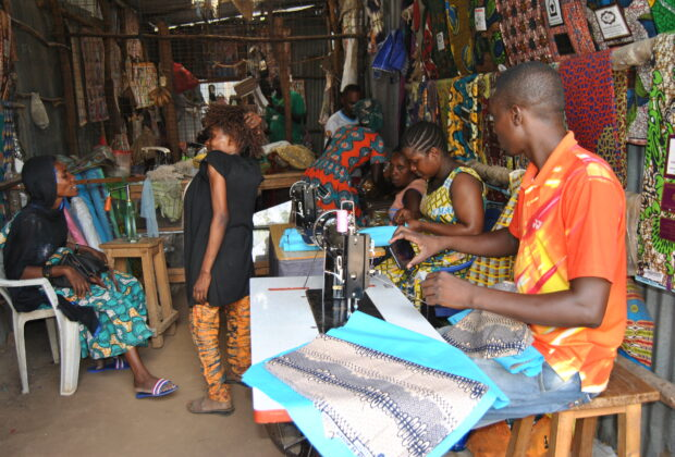 Biclere (standing) talks to a cliet at her shop while her employees work on other clothes.