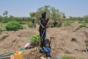 Ramadhan Hassan rides a water pump at Choro farm in Kakuma camp to water his farm.