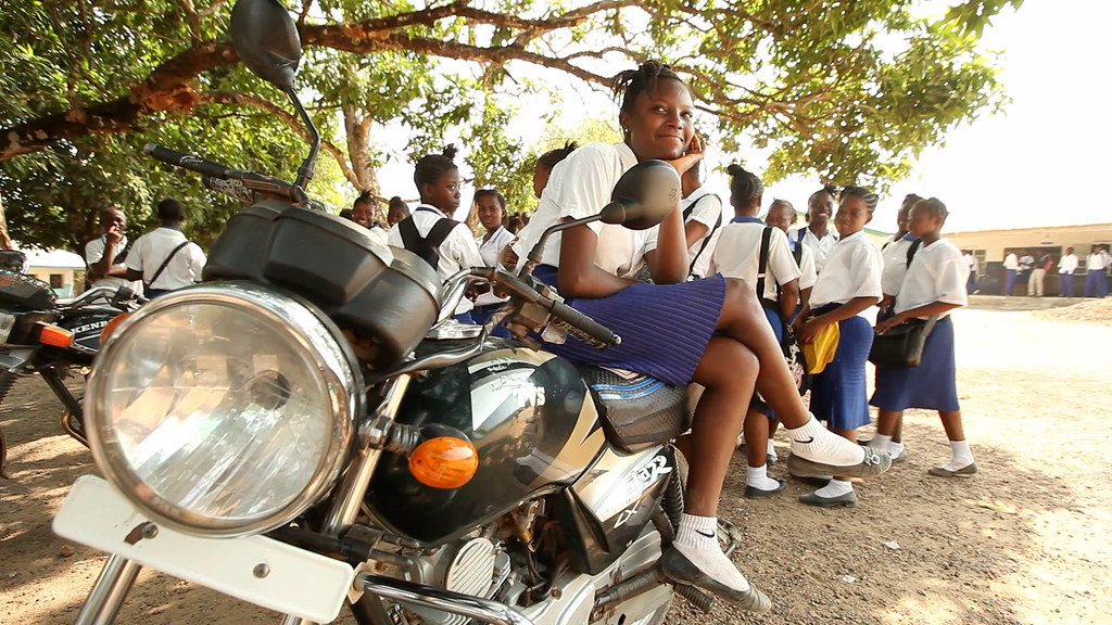 Sierra Leone pregnant school girl ban: A school girl in Sierra Leone sits on a motorcycle. Credit: GPE/Stephan Bachenheimer
