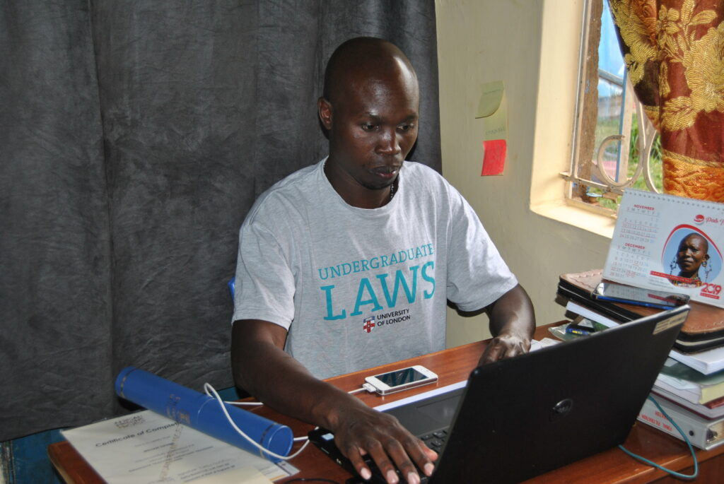 William Okumu working on his computer at his house. Credit: Dominic Kirui.
