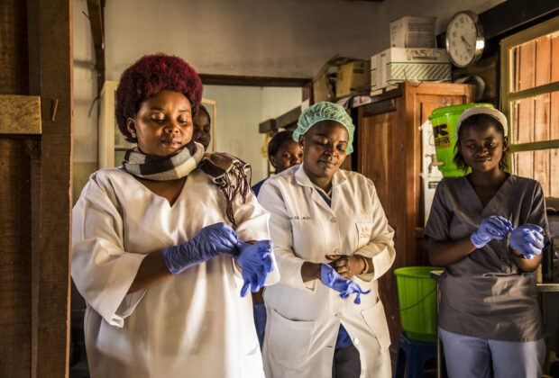 Abuja Declaration. Health workers in the DRC put on gloves on before checking patients at the hospital.