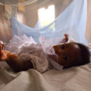 An infant surrounded by malaria bed net in Ghana. Credit: Arne Hoel / World Bank.