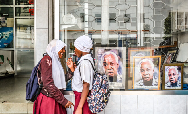 two school girls stand outside a shop in Arusha, Tanzania, with framed photos of Julius Nyerere displayed. Credit: Jaclynn Ashly.