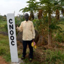 east africa pipeline Okecha Cibojo, a farmer in Nyamtai village, Kikuube District in Western region of Uganda standing by CNOOC beacons marking the route of a feeder pipeline for Kingfisher project. Credit: Maina Waruru.