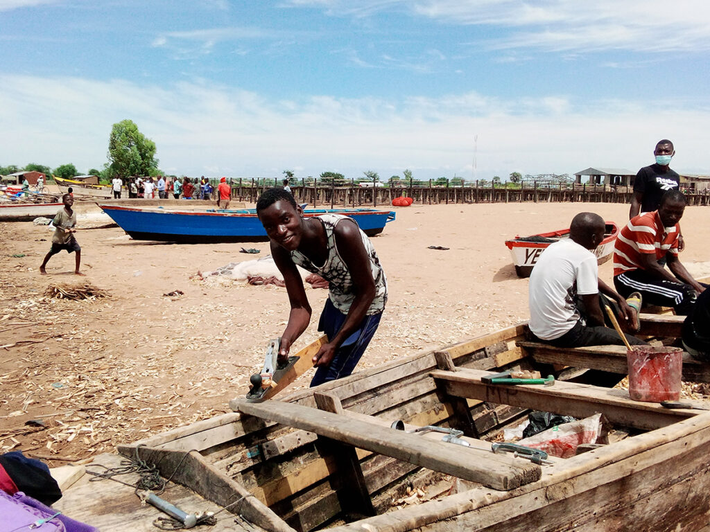 Fixing boats on Chikombe beach before the journey. Credit: Charles Pensulo.